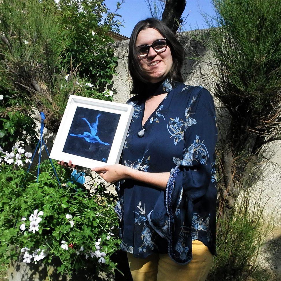 """L'artiste peintre et dessinatrice Margot Barbier tenant son oeuvre """"Envolée nocturne"""""""